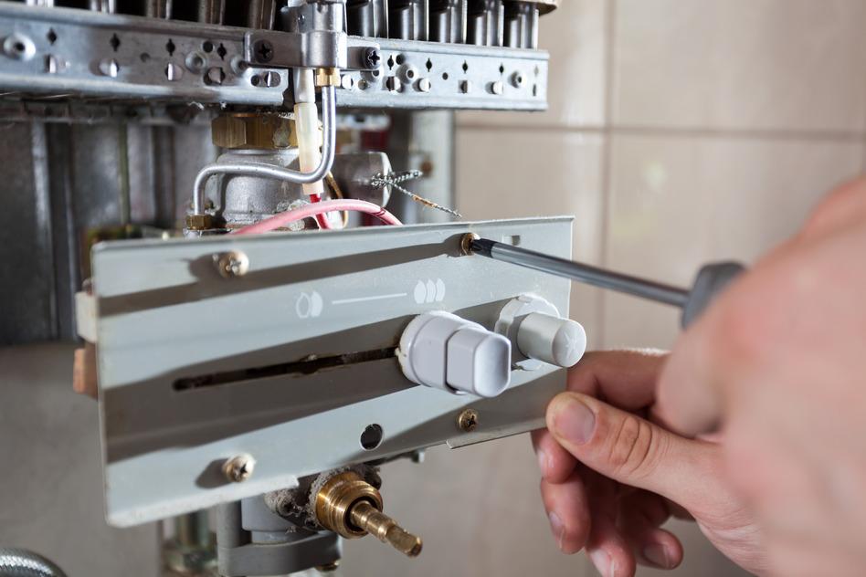 Repairman adjusting gas water heater